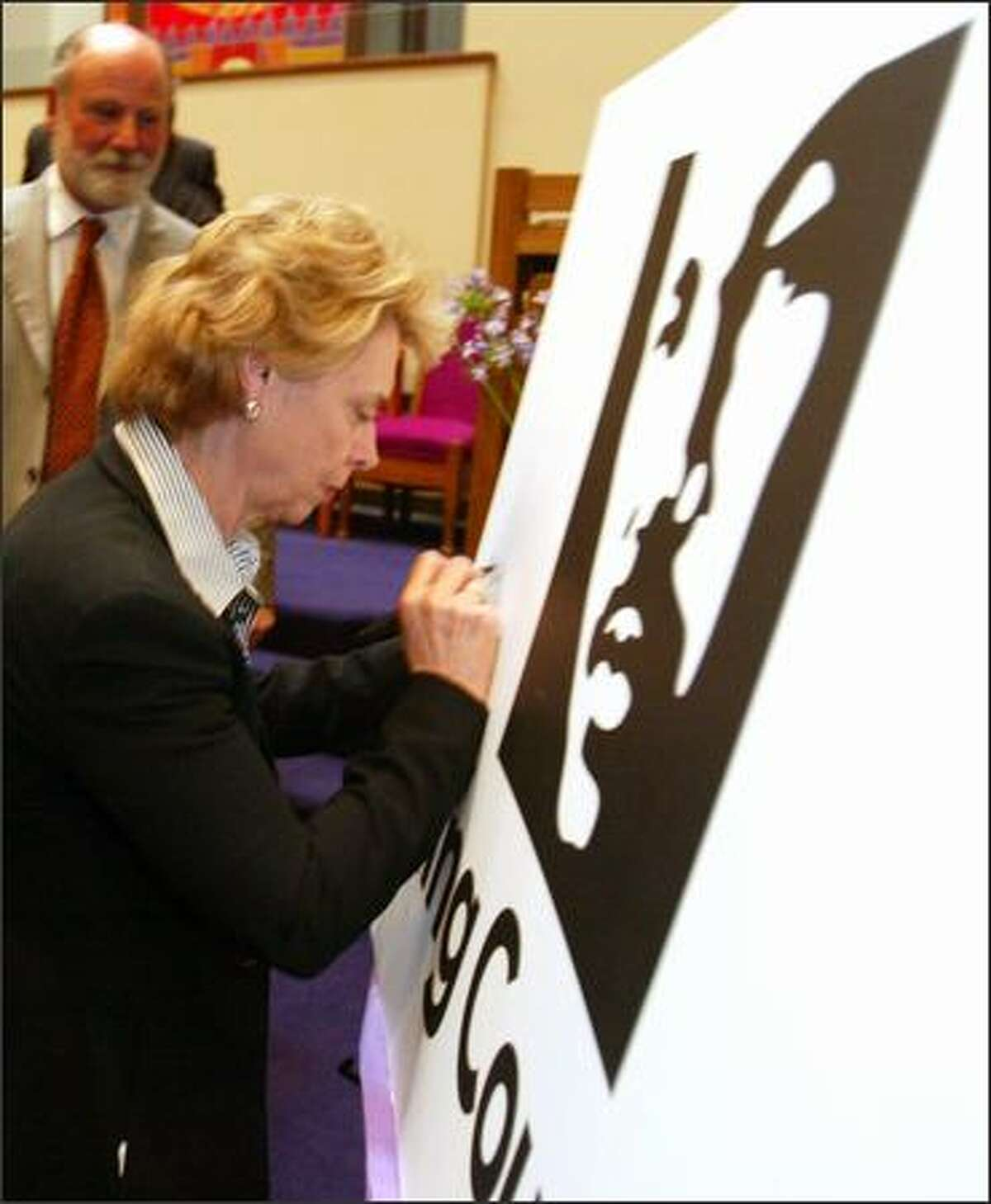 Gov. Chris Gregoire signs a poster showing the proposed new logo for King County, which depicts the county's namesake, the Rev. Martin Luther King Jr. The logo was unveiled at Mount Zion Baptist Church in Seattle on Sunday.