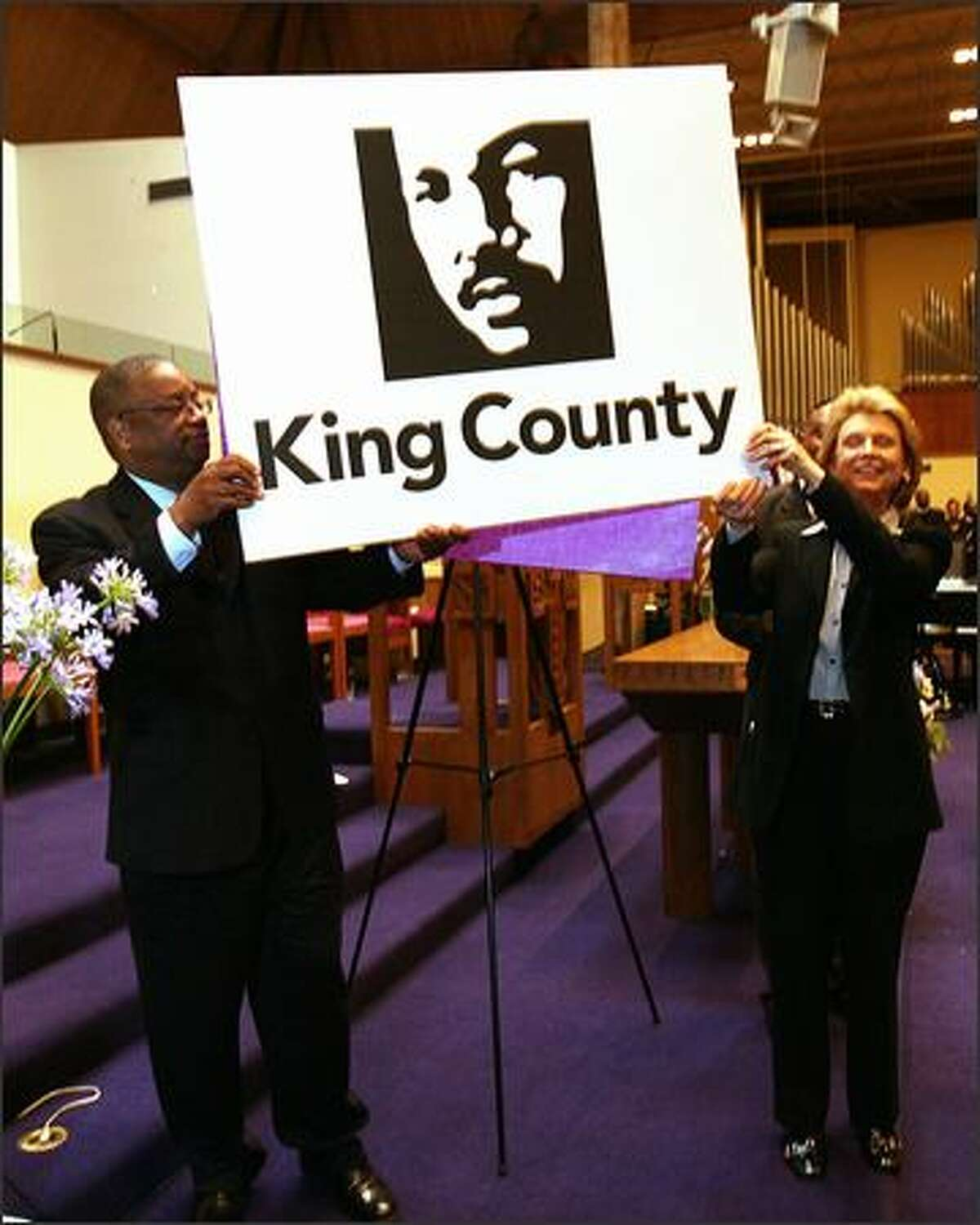 King County Council Chairman Larry Gossett and Gov. Chris Gregoire show the county's proposed logo of the Rev. Martin Luther King Jr. outside Mount Zion Baptist Church in Seattle on Sunday.