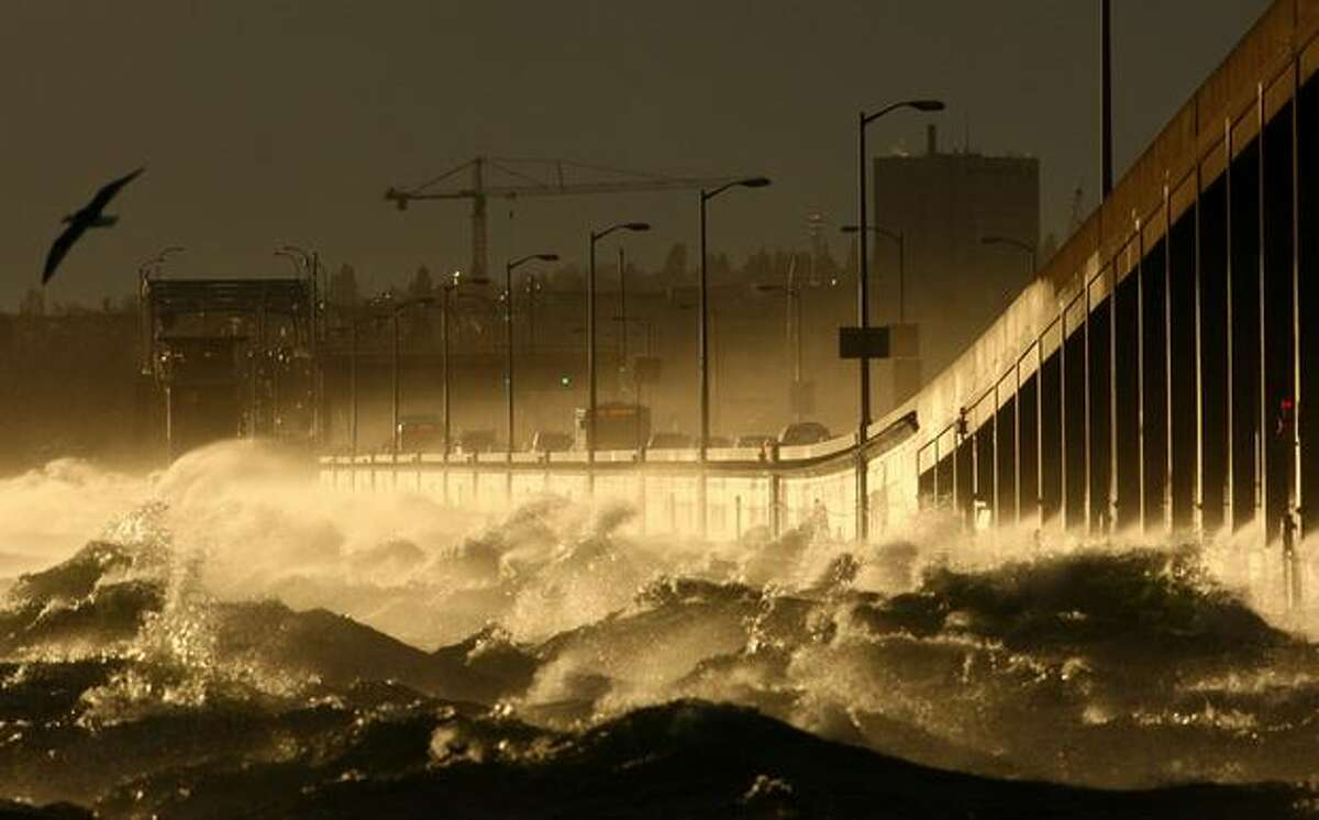 Waves crash against the State Route 520 Bridge as the sun sets over Lake Washington in Seattle during a windstorm on Thursday, March 10, 2011. Winds gusting to 50 mph slowed traffic to a crawl during the evening commute and waves dumped water on cars stuck on the bridge. The aging structure closes when gusts reach 50 mph for a 15 minute period, a criteria not met Thursday.