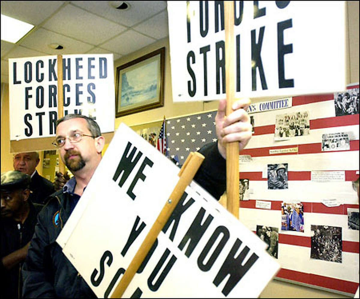 Jeff DeBord, foreground, joins other members of the Machinists' Local 709 in Marietta, Ga., as they gather picket signs after voting to strike Lockheed.