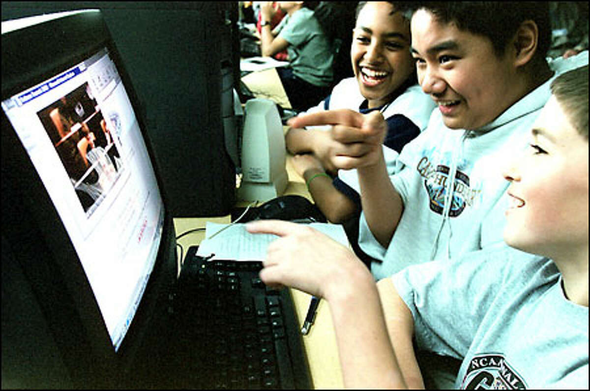 McClure Middle School sixth-graders Colin Dunphy, foreground; Tim Ramos, center; and Haben Sebhatu get a kick out of seeing one of their classmates on an online videoconference hookup from an international salmon summit.