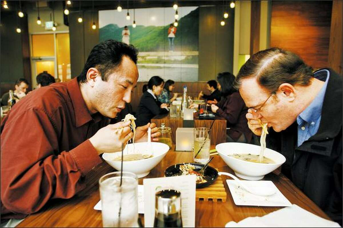 Masaki Miyagi and Michael Faris slurp their noodle lunches at Boom Noodle, which opened in January.