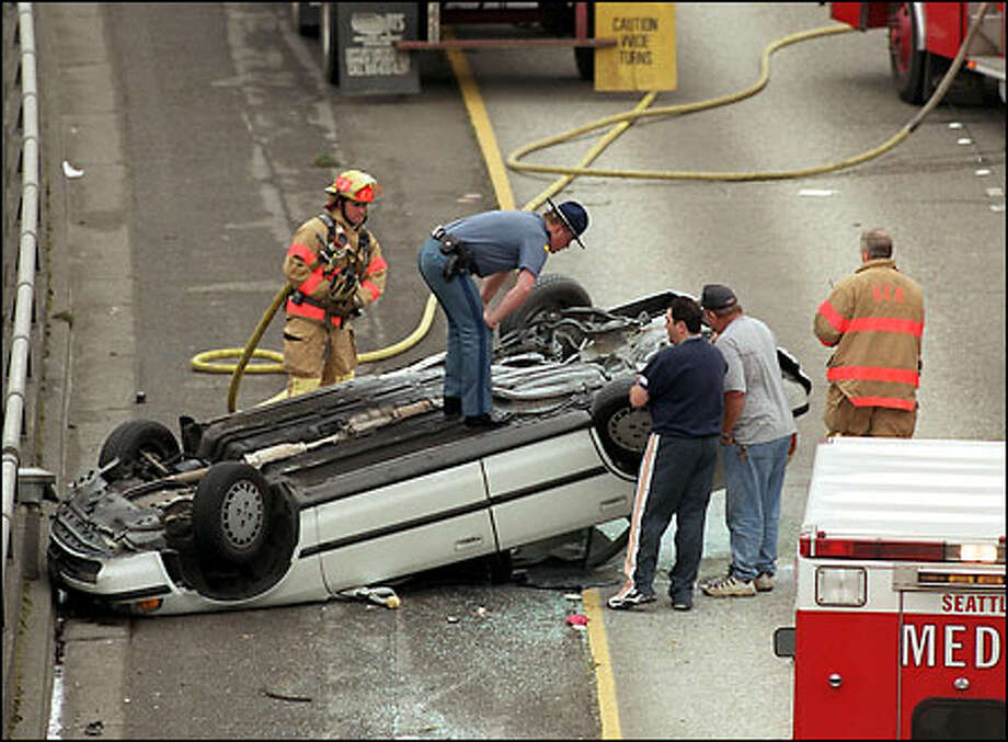 CAR ACCIDENT: To get a better look, a Washington state trooper stands on top of an overturned car in the northbound lanes of Interstate 5 near the Lake City exit yesterday. One woman was taken to Harborview Medical Center. Photo: Gilbert W. Arias, Seattle Post-Intelligencer / Seattle Post-Intelligencer