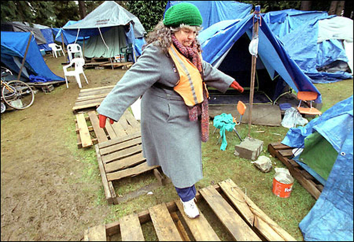 Pam Packard keeps her balance while stepping over some wooden planks to avoid the mud as she walks security at Tent City in North Seattle.