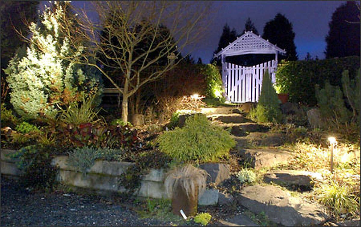 Low-voltage downlighting gives the effect of moonlight spilling on the ground, creating pools of light at the base of two arbors in the garden of Dave and Carol Ager's home in Woodinville.