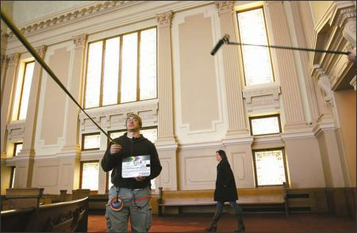 """Nacime Khemis measures the camera distance while actress Elisabeth Rohm rehearses recently during filming of """"The Spy and the Sparrow"""" at the First Church of Christ, Scientist, on Capitol Hill. Developers who are turning the sanctuary into condos delayed construction to allow the film crew to use the building."""