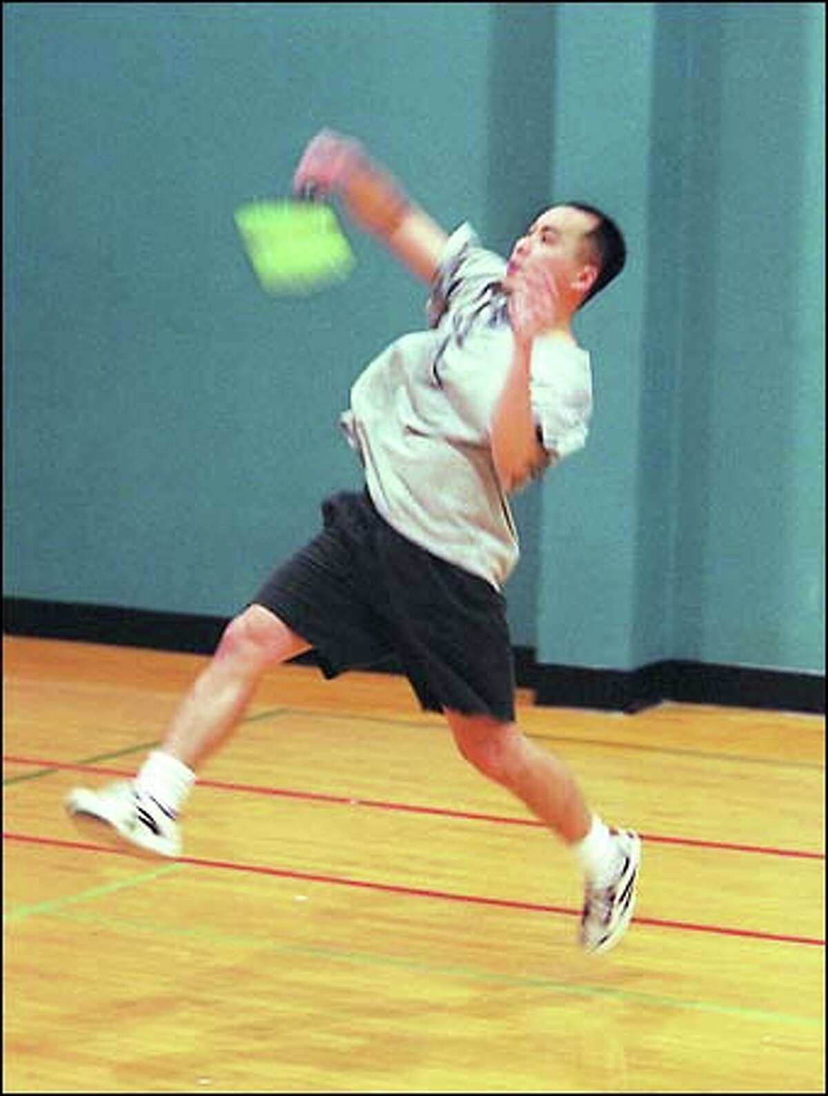 Federal Way podiatrist Andrew Soo, who holds state badminton titles in singles and doubles, leaves his feet during a practice at the Seattle Badminton Club.