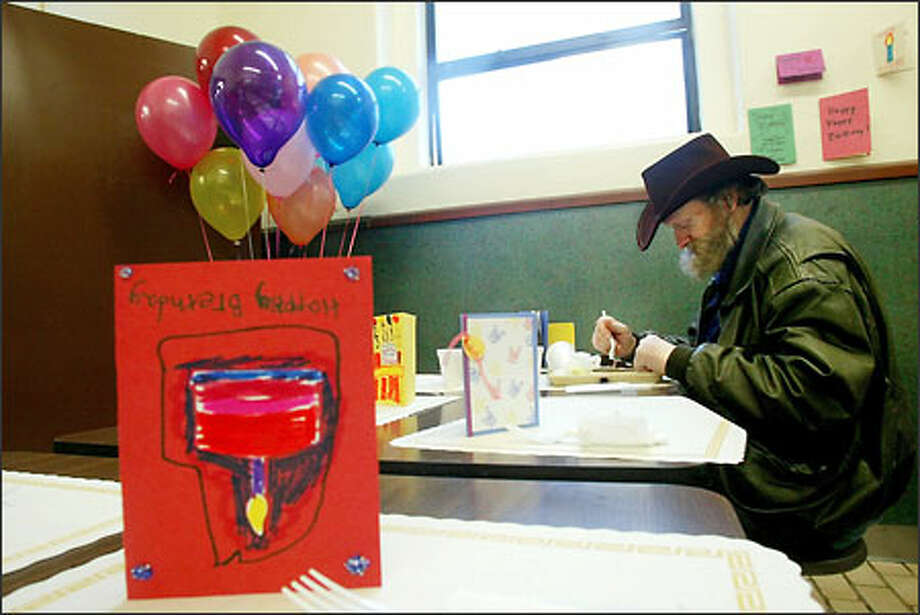 Michael Dupuis, born Feb. 14, 1953, is the last to leave the table as he enjoys his birthday cake at the Union Gospel Mission's birthday party, which it organized for all its clients. Photo: Dan DeLong, Seattle Post-Intelligencer / Seattle Post-Intelligencer
