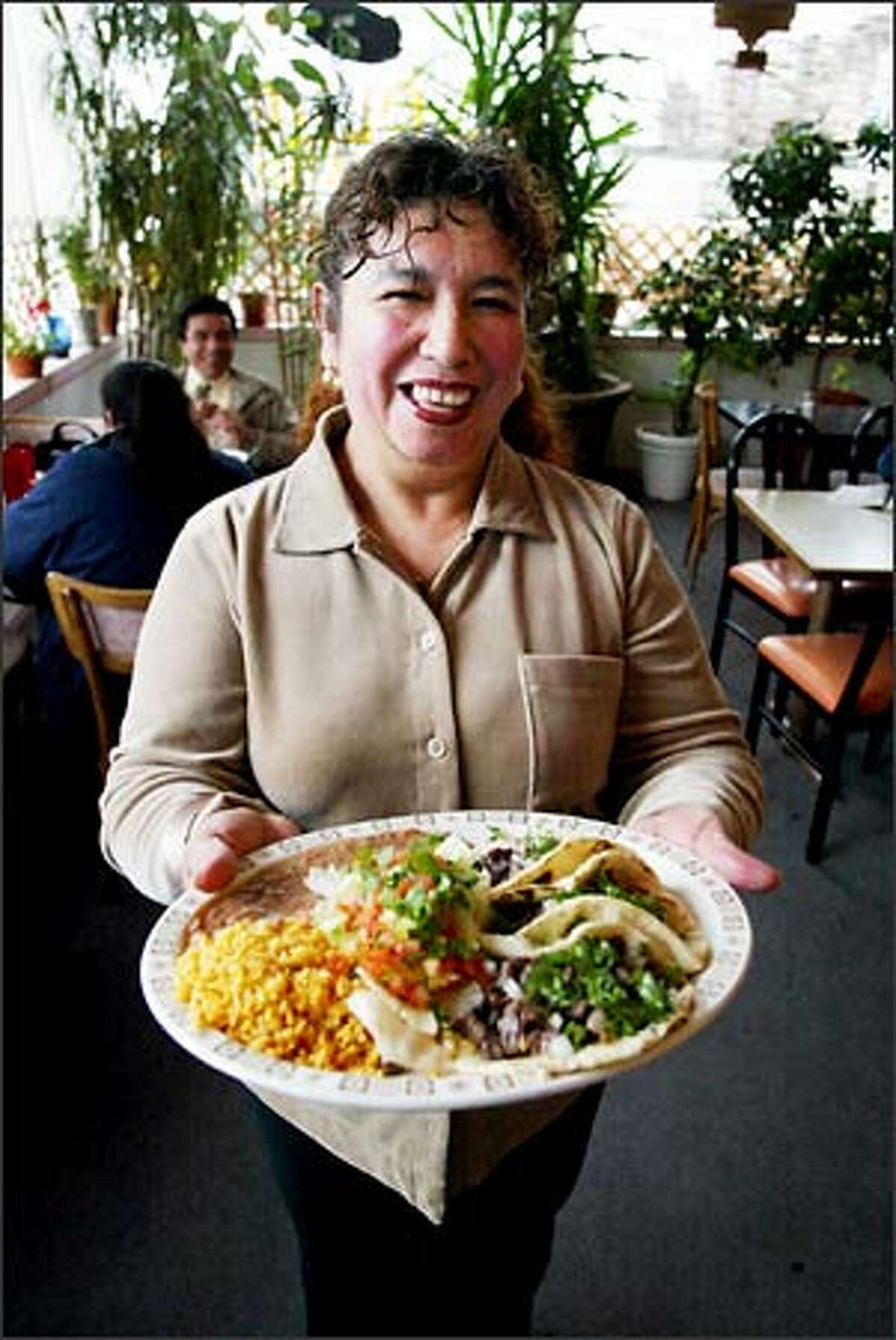 Elvira Lohman, owner of Coliman Restaurant & Taqueria in Georgetown, shows off one of her signature dishes, a steaming plateful of Tacos de Carne Asada.