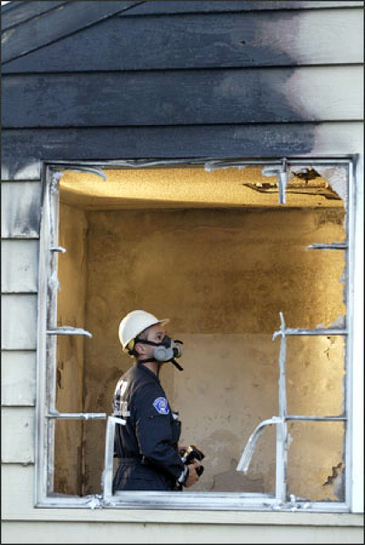 Fire investigator Joe Rexach inspects damage to a Kirkland church yesterday.