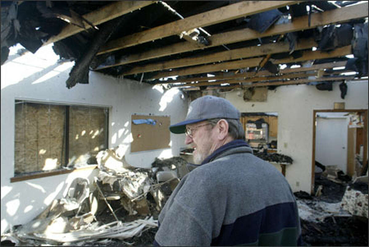 Pastor Mike Holcombe surveys the damage to Grace Missionary Baptist Church in Tacoma after an early-morning fire destroyed the building.