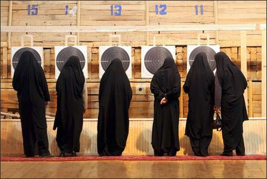 Wearing chadors, Iranian female paramilitary volunteers, Basiji, check the targets after shooting in a competition in Tehran. (AP Photo/Vahid Salemi) Photo: Associated Press / Associated Press