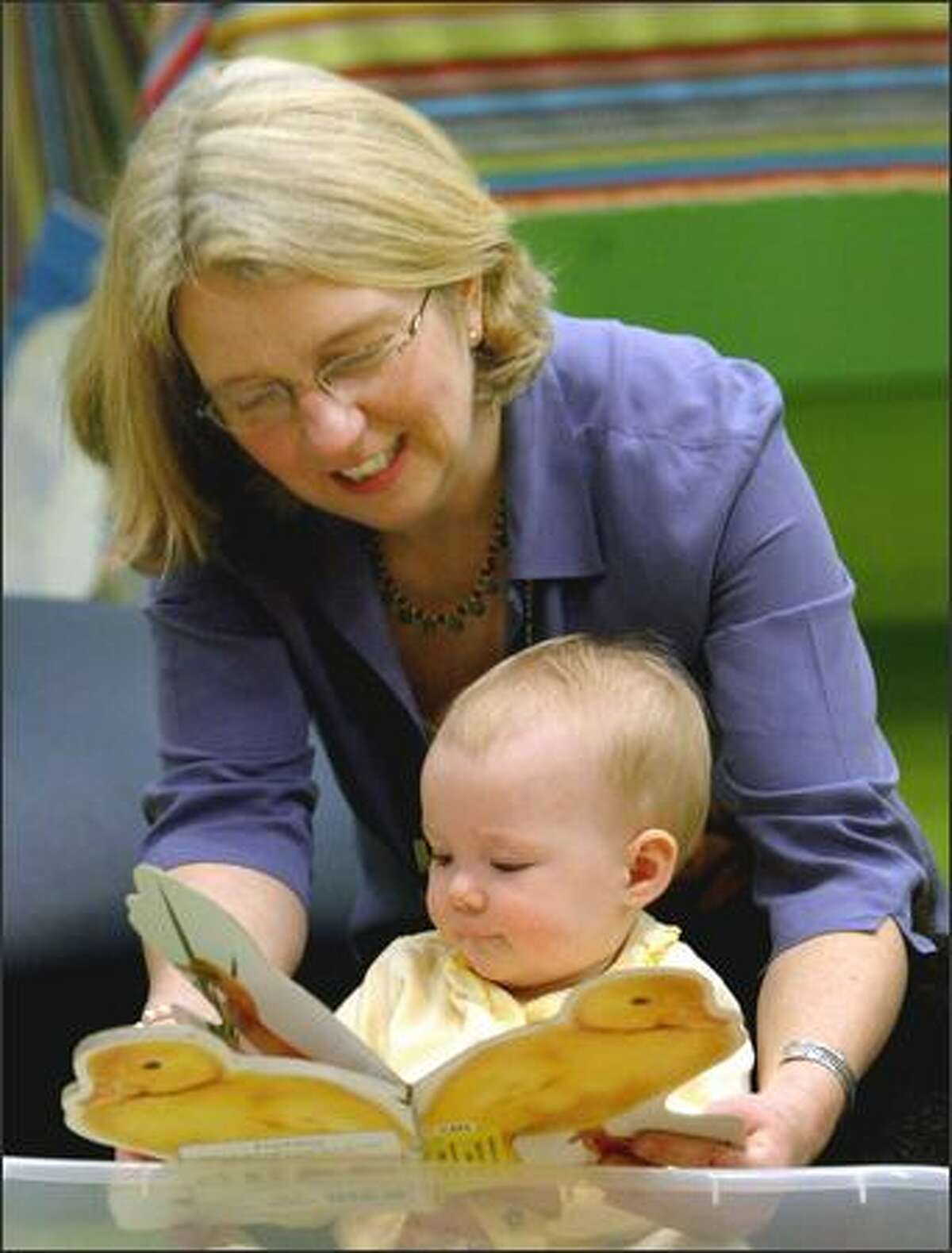 Betsy Cluck-Keil reads a book to 10-moth-old Sophia Price while she teaches parents how to read to their infants.