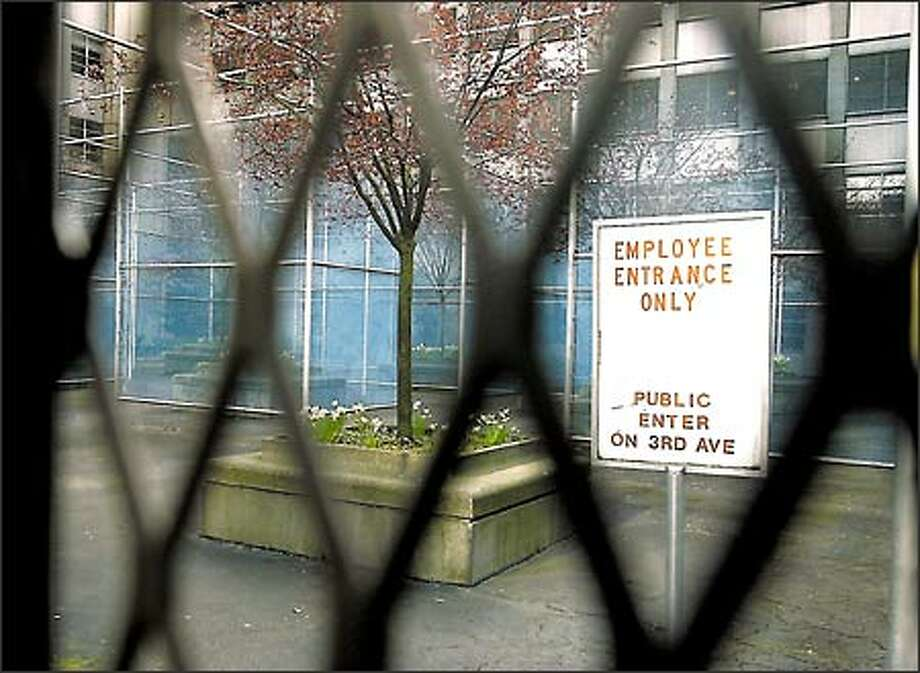 "Viewed now only through the bars of a locked gate, Robert Irwin's installation ""Nine Spaces, Nine Trees"" was designed as a private space in a public area, with plum trees at the center of nine transparent ""rooms,"" made of blue chain-link fence. The fences were supposed to be a blur of color in the atmosphere. Photo: Gilbert W. Arias, Seattle Post-Intelligencer / Seattle Post-Intelligencer"