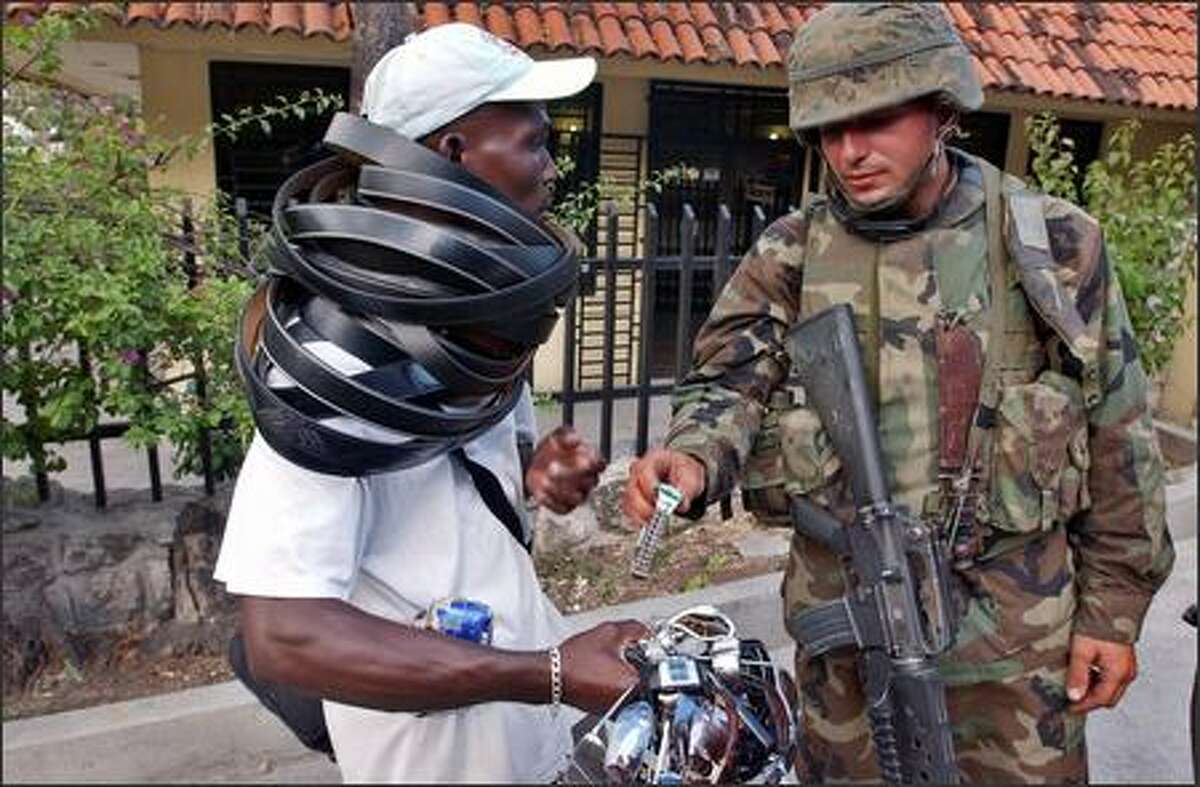 A U.S. Marine inspects a watch from a man selling watches, sunglasses and belts in Petionville, Haiti. (AP Photo/Dario Lopez-Mills)