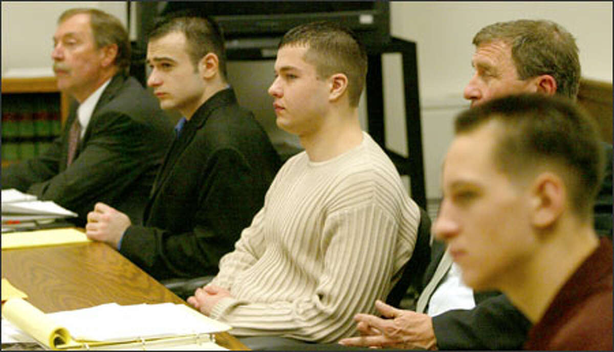 The defendants and their attorneys -- from left, attorney Tom Olmstead, Vadim Samusenko, David Kravchenko, attorney Tim McGarry and Yevgeniy Savchak -- listen to the cross-examination of Micah Painter yesterday.
