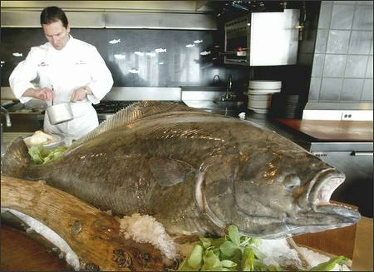 Chef Pat Donahue prepares an order of alder planked halibut behind a display of a 55-pound halibut at Anthony's Pier 66.