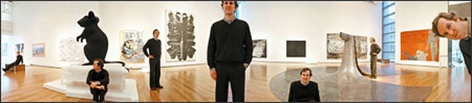 "In this panorama photo, Michael Darling, curator of contemporary art in the new Wright Galleries for Modern and Contemporary Art, is shown with, from left: ""Black Series: Coulures Noires"" by Ghada Amer; ""To Add One Meter to an Anonymous Mountain"" by Zhang Huan; ""Blue and Gold in Short Skirt"" by Sue Williams; ""Mann und Maus"" by Katharina Fritsch; ""On the Wall Above"" by Sean Landers; ""Rorschach"" by Andy Warhol; ""An Exhibition of Gasoline Powered Engines"" by Ed Ruscha; ""Stranger in the Village (Excerpt) #7"" by Glenn Ligon; ""Some/One"" by Do-Ho Suh; ""Die Welle (Wave)"" by Anselm Kiefer and ""White Squad II"" by Leon Golub. Photo: Mike Urban, Seattle Post-Intelligencer / Seattle Post-Intelligencer"