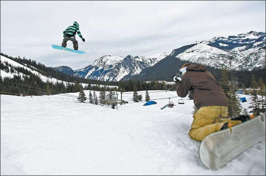 Justin Hanson makes a video record of his friend Garrett Richardson launching off a large jump Sunday in Central Park at the Summit at Snoqualmie. Photo: Mike Kane, Seattle Post-Intelligencer / Seattle Post-Intelligencer