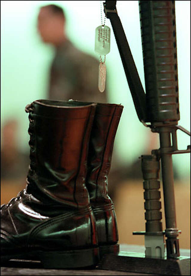 Inside the Soldiers' Chapel at Fort Lewis, the symbolic boots, dog tags and inverted rifle with helmet form the centerpiece at a memorial yesterday for 29-year-old Army Spc. specialist Jason Wildfong, who was one of six military observers, including five Americans, killed by friendly fire during a training accident in Kuwait on Monday. Photo: Gilbert W. Arias, Seattle Post-Intelligencer / Seattle Post-Intelligencer