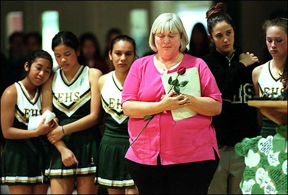 Evergreen High School cheerleading coach Terry Dixon and her squad, which just last week included Josie Grace Peterson, listen to Mary Sam sing