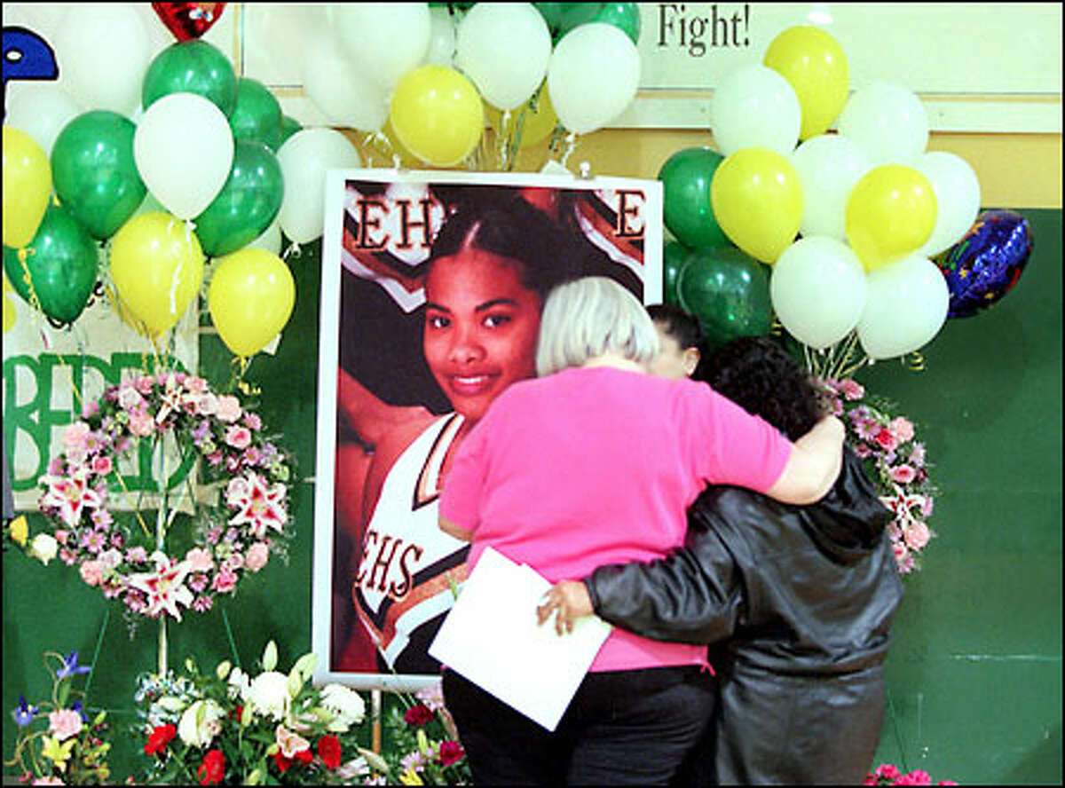 Evergreen High School cheerleading coach Terry Dixon, left, hugs Josie Grace Peterson's mother, Mary Marrero, in front of a photo of Peterson.