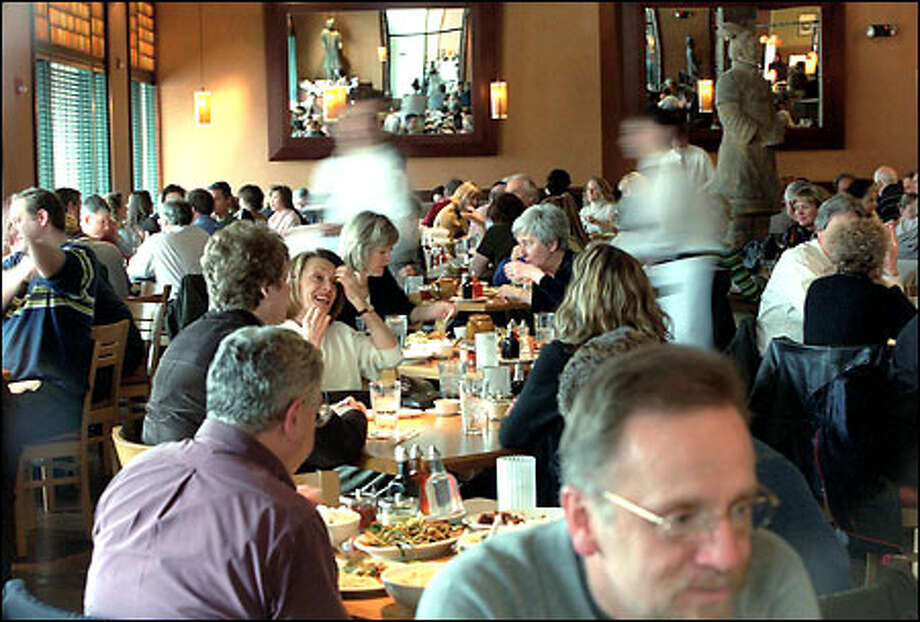 Servers move through P.F. Chang's in downtown Bellevue. Joining the collection of restaurants soon will be Red Robin and possibly Ruth's Chris Steakhouse. Photo: Phil H. Webber, Seattle Post-Intelligencer / Seattle Post-Intelligencer