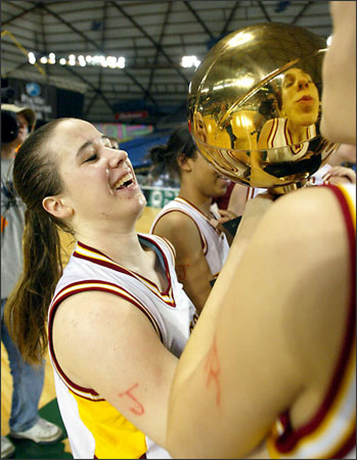 Prairie's Lauren Short, left, holds the trophy as teammate Jessica Menkens, right, prepares to plant a kiss on it after the team's 44-39 win over Central Valley in the girls Washington Class 4A championship game.
