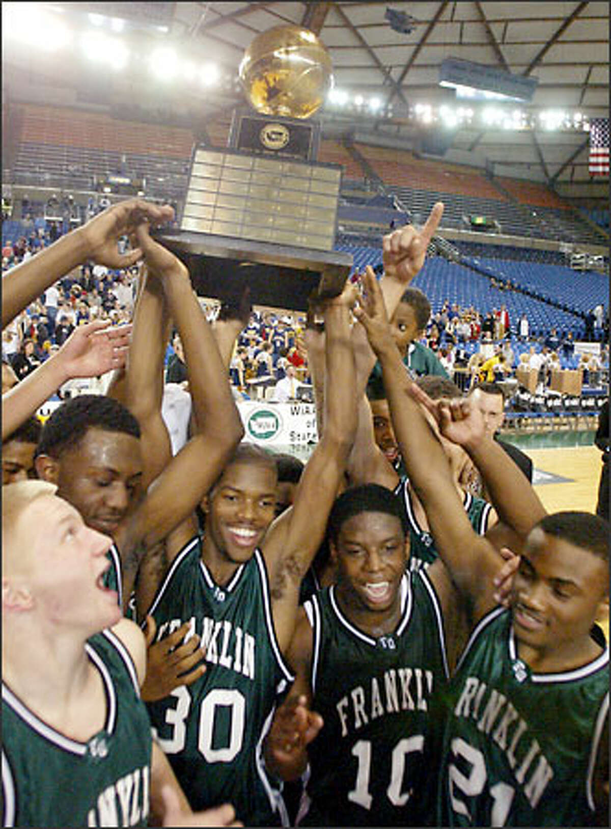 Franklin's Aaron Brooks (30), Senrique Tellez (10), Jordan Daisy (21) and others hold up the trophy after Franklin beat Mead 67-55 to win the boys Washington Class 4A basketball championship.