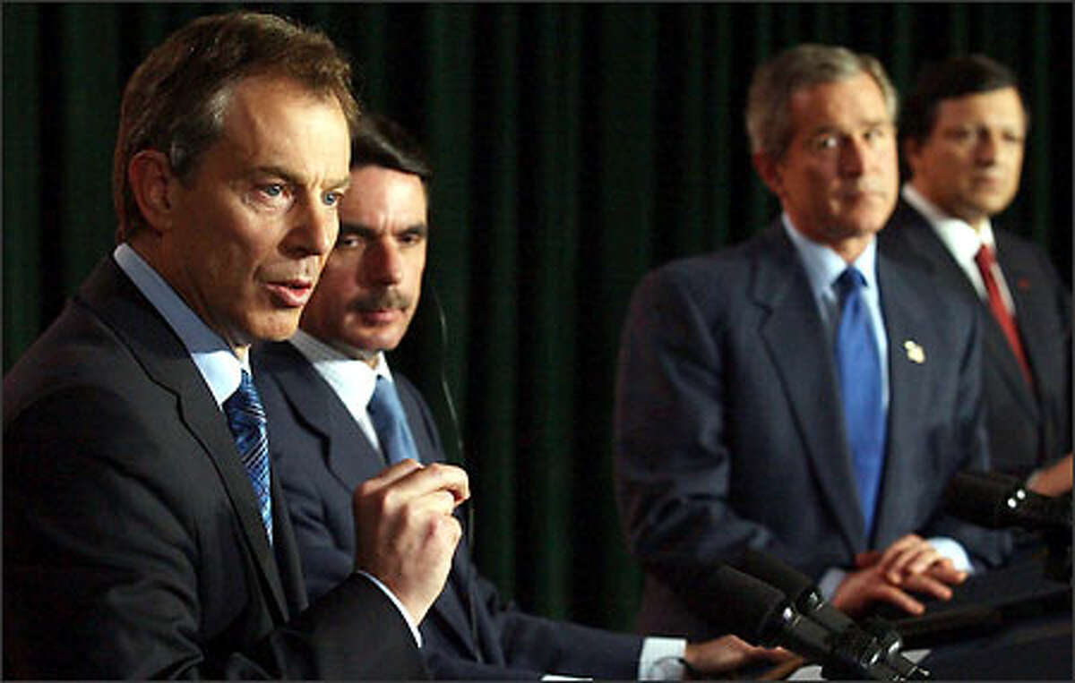 British Prime Minister Tony Blair, far left, Spanish Prime Minister Jose Maria Aznar, President George W. Bush and Portuguese Prime Minister Jose Manuel Durao Barroso face reporters after a diplmoatic conference on the island of Terceira in the Azores.