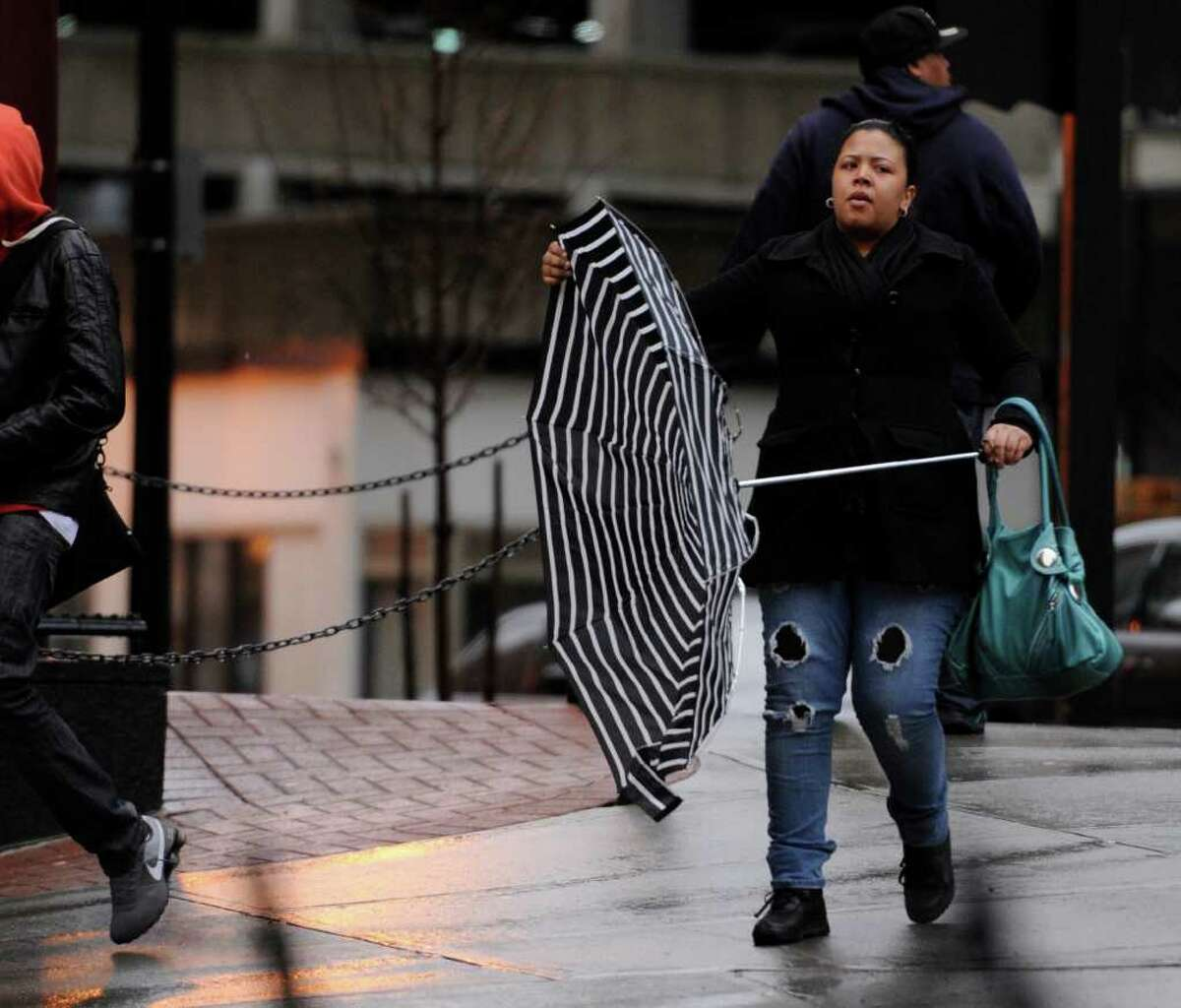 A pedestrian fights with an umbrella in downtown Albany, New York, on April 5, 2011, on a rainy, blustery day. (Skip Dickstein / Times Union)