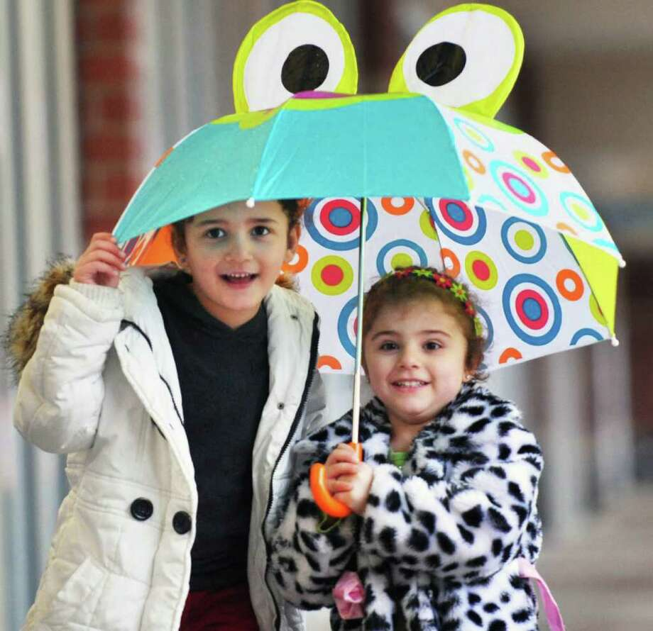 Riwa, 5, and Rhea Frangich, 3, of Latham huddle under an umbrella during a shopping trip with their mother at Latham Farms on Tuesday morning, April 5, 2011.   (John Carl D'Annibale / Times Union) Photo: John Carl D'Annibale / 00012643A