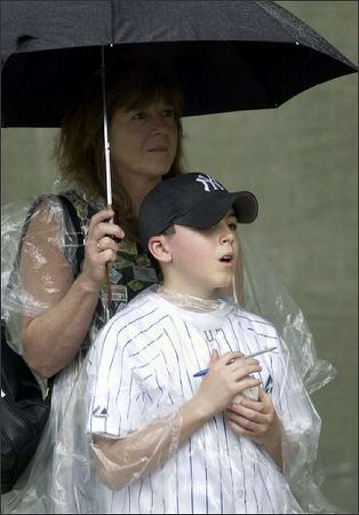 Peter Anspach, 11, of Wilton, Conn., stands with his mother Rita outside Progress Engery Park in St. Petersburg, Fla., with hopes of getting some autographs after a spring training game between the New York Yankees and the Tampa Bay Devil Rays was rained out. (AP Photo/Tom E. Puskar)