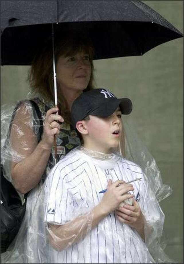 Peter Anspach, 11, of Wilton, Conn., stands with his mother Rita outside Progress Engery Park in St. Petersburg, Fla., with hopes of getting some autographs after a spring training game between the New York Yankees and the Tampa Bay Devil Rays was rained out. (AP Photo/Tom E. Puskar) Photo: Associated Press / Associated Press