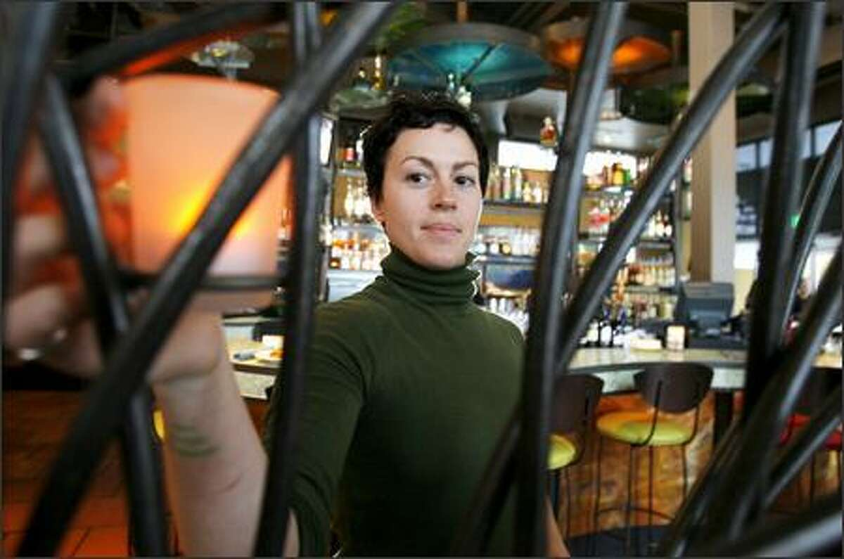 Restaurant manager Rachel Spivey places a candle on the decorative iron railing at Cactus. The restaurant is like a trip to the tropics, even during the rainy wintertime.