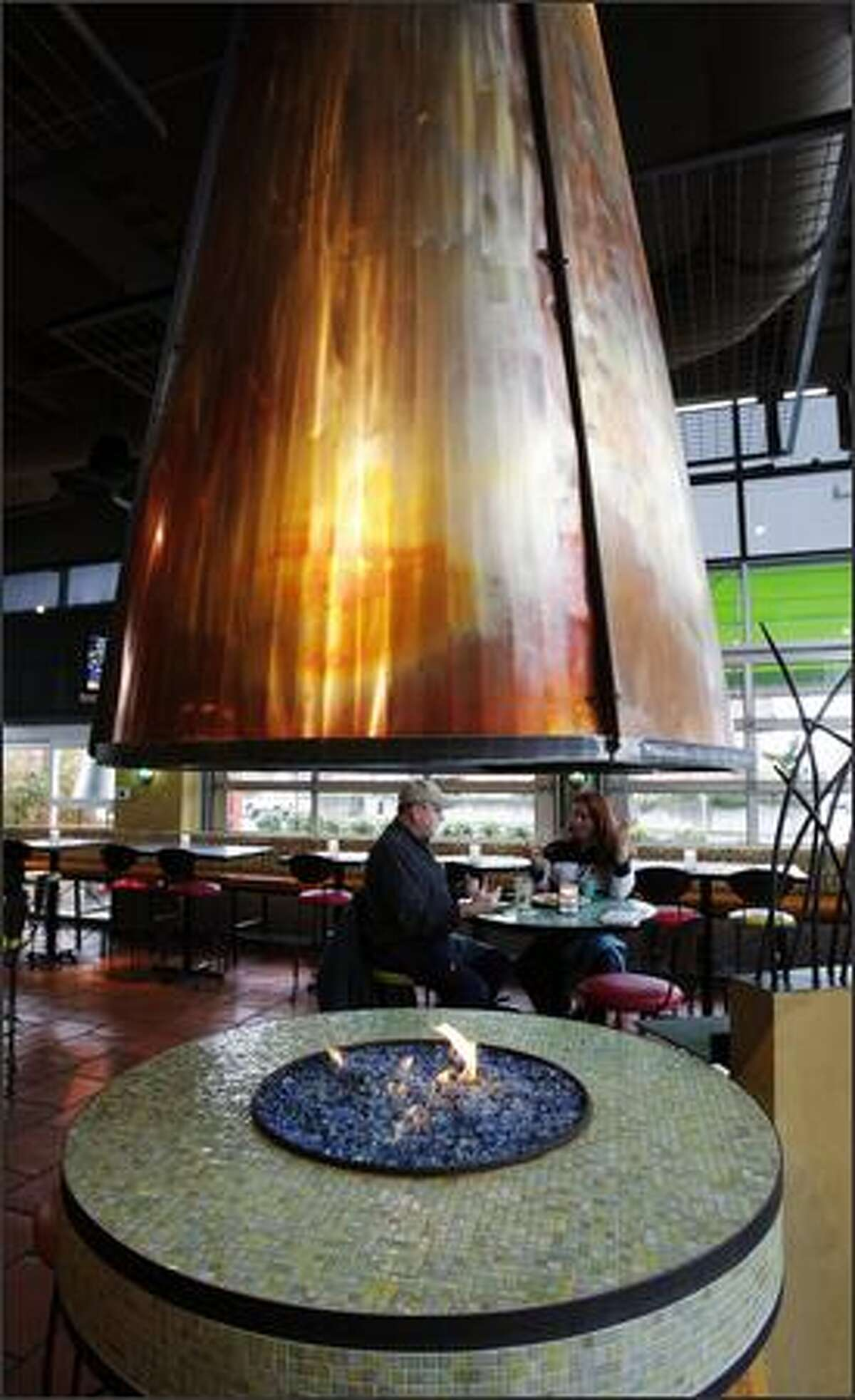 Charles O'Brien and Paula O'Neill enjoy their lunch near the fireplace at the Alki Cactus, the third in the Seattle area.