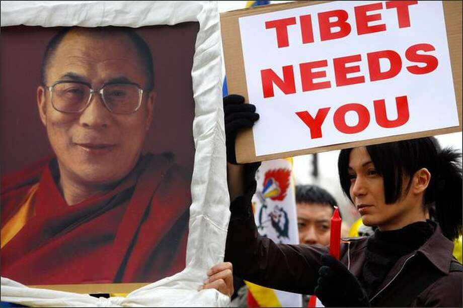 "An activist of the France Tibet association, right, standing by a photo of the Dalai Lama, takes part to a demonstration against the violence in Tibet, Sunday, near the Chinese embassy in Paris. Violence spilled over from Tibet into neighboring provinces Sunday as Tibetan protesters defied a Chinese government crackdown while the Dalai Lama warned that the area faced ""cultural genocide"" and appealed to the world for help. (AP Photo/Jacques Brinon) Photo: Associated Press / Associated Press"