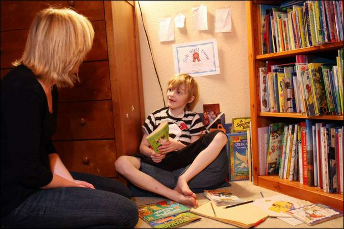 Camden Dalpez, 7, reads with his mom, Jena Dalpez, at their Bothell home. Dalpez says Camden's health issues can be traced to a vaccine.