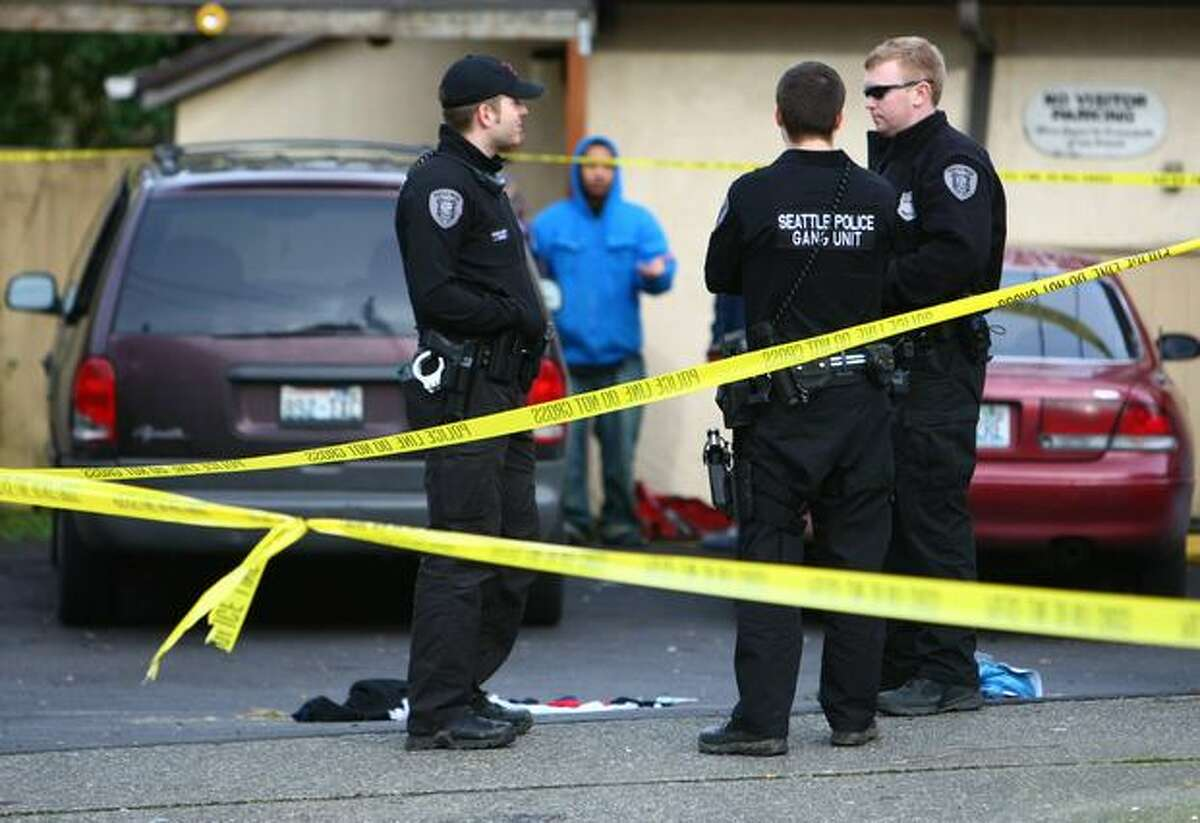 Seattle Police Gang Unit officers work the scene after a man was shot in the chest on Wednesday in the 9300 block of 51st Avenue South in Seattle.