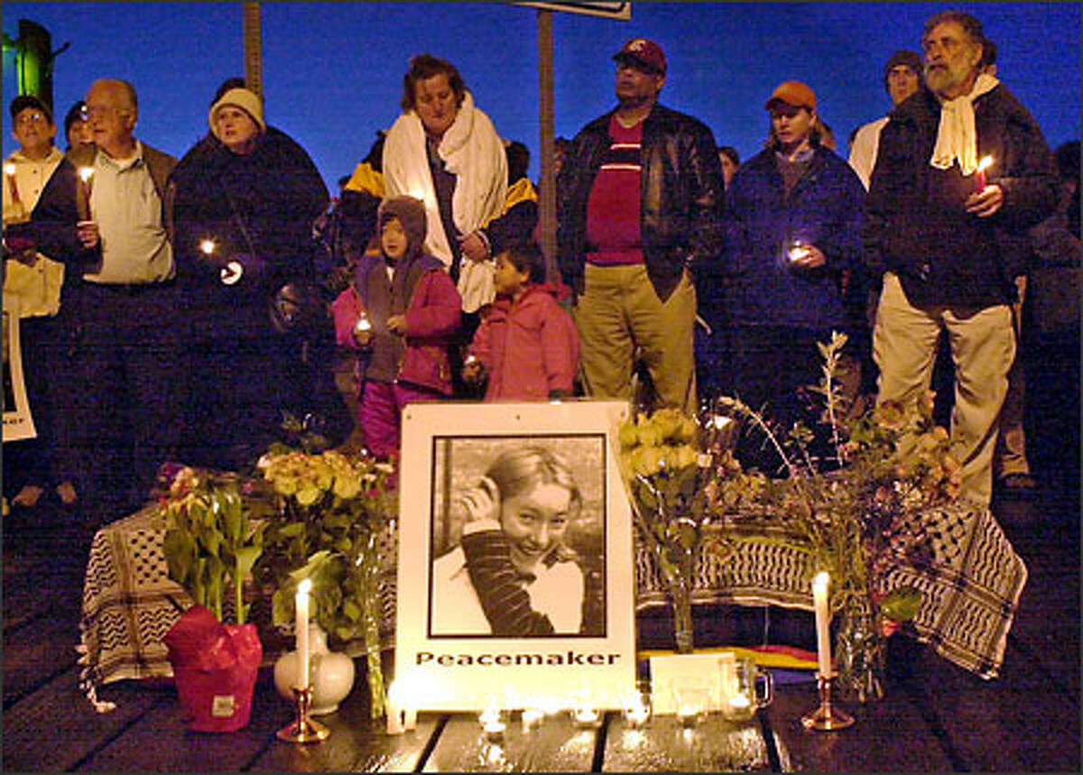 Residents stand in silent vigil around a mock casket at a candlelight vigil Sunday evening, March 16, 2003, for Rachel Corrie, 23, a student at The Evergreen State College in Olympia.