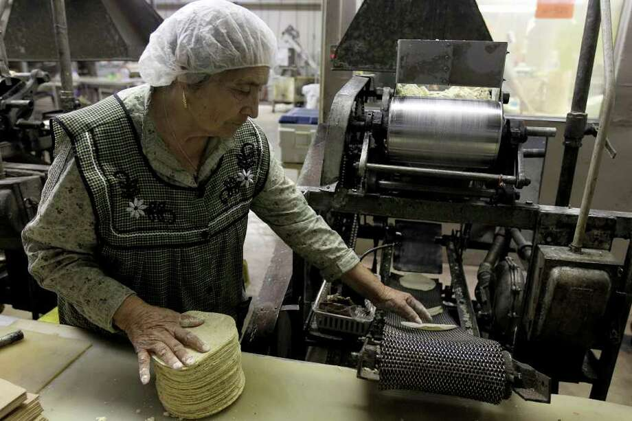 Tortilla maker Filipa Conchas, who has worked at Sanitary for 34 years, stacks tortillas from one of the machines brought from Mexico in the 1920's at the Sanitary Tortilla Factory, March 23, 2011.  (Jennifer Whitney/Special to the San Antonio Express-News) Photo: Special To The Express-News / special to the San Antonio Express-News