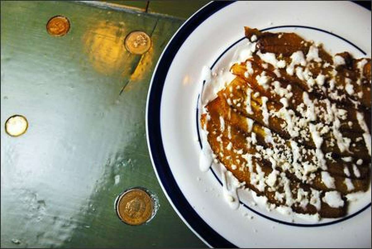 The Platanos Machos dessert made with fried plantains sits on the bar embedded with old Mexican coins. The desserts and appetizers are some of the best items on the menu.