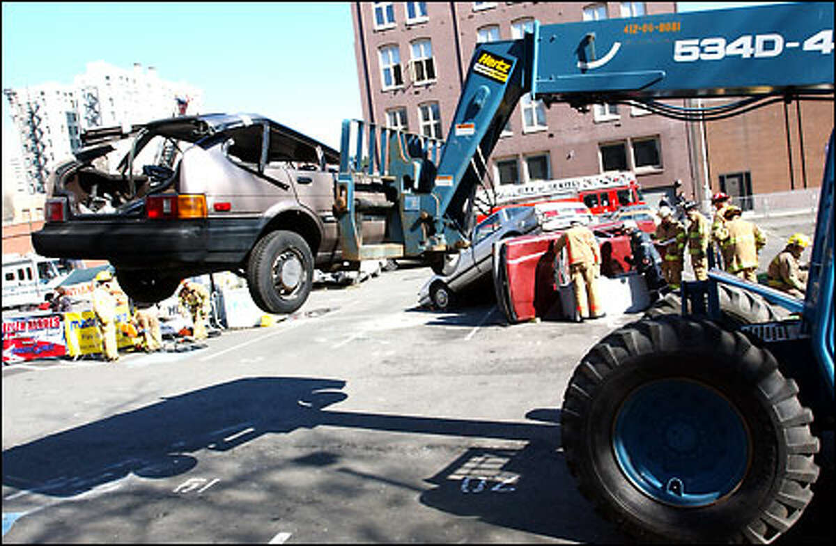 One of the wrecked cars is removed from the training area in Pioneer Square during a rescue competition.
