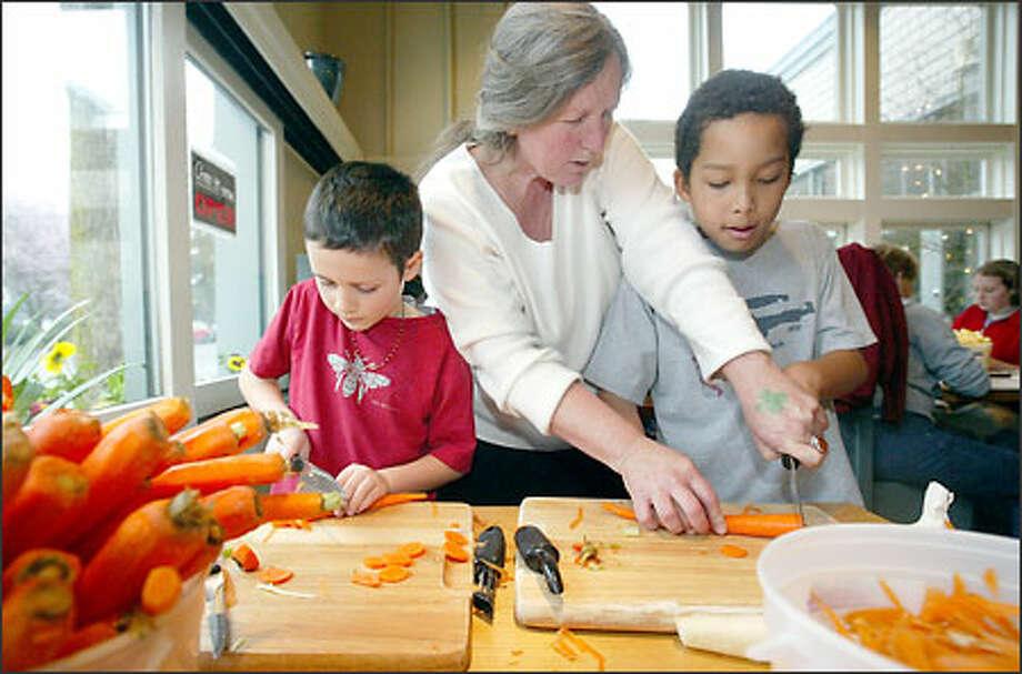 Teacher Kimberly Buchanan helps pupils Skiah Garcia, left, and Kwame Salmi-Adubofour cut vegetables at St. Clouds restaurant in Madrona. Photo: Dan DeLong, Seattle Post-Intelligencer / Seattle Post-Intelligencer