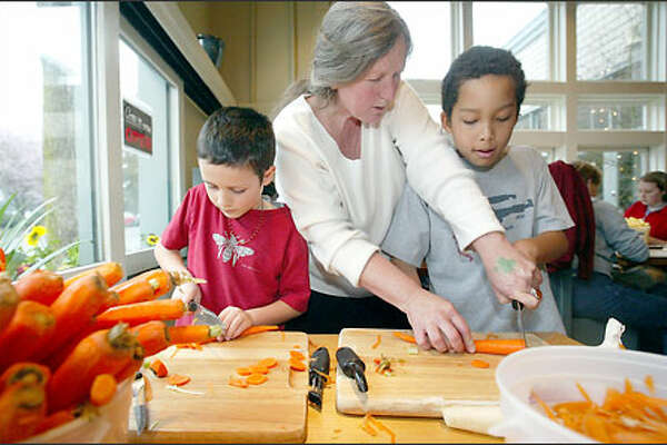 Teacher Kimberly Buchanan helps pupils Skiah Garcia, left, and Kwame Salmi-Adubofour cut vegetables at St. Clouds restaurant in Madrona.