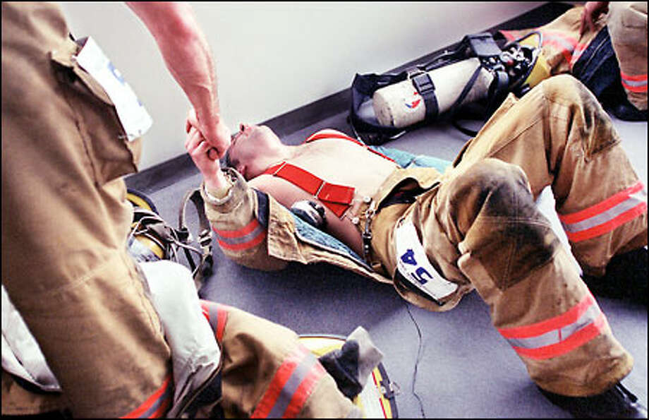 "Keith Taylor, right, of the Marysville Fire Department is congratulated by a teammate after climbing 69 flights of stairs in full gear with oxygen during the 10th annual Safeco firefighter challenge to benefit The Leukemia & Lymphoma Society. About 500 firefighters participated in the event at the Bank of America Tower in downtown Seattle yesterday. Taylor, who has made the climb six or seven times, said ""it's getting harder, maybe because I just turned 30."" Photo: Renee C. Byer, Seattle Post-Intelligencer / Seattle Post-Intelligencer"