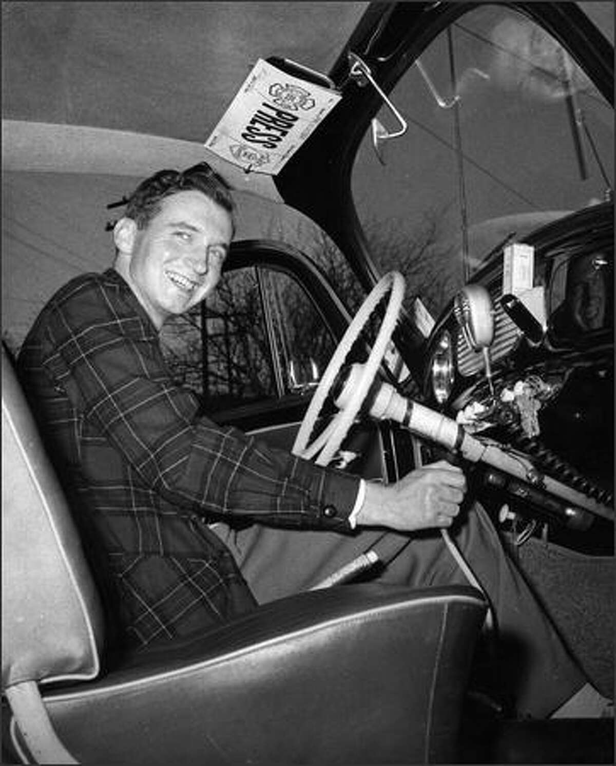 Phil H. Webber sitting in his Volkswagen in 1958.