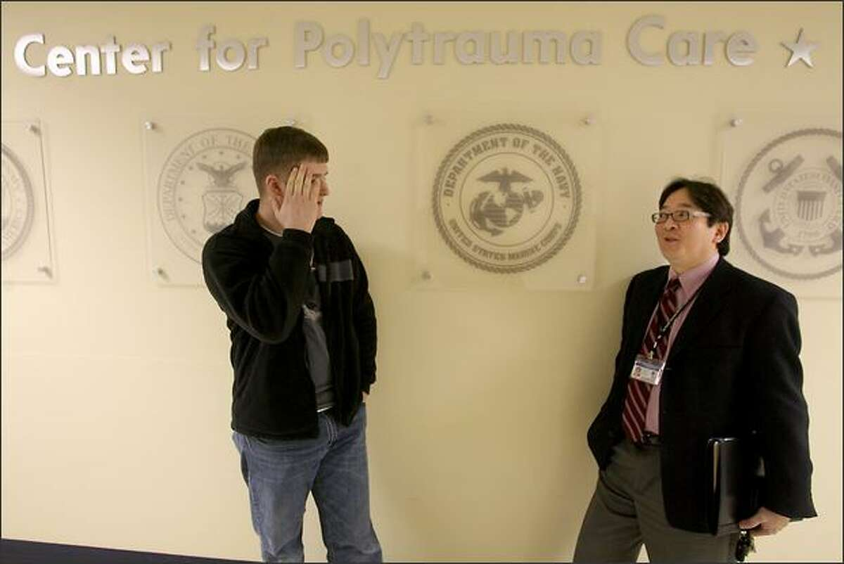 Dr. Jay Uomoto talks with Bradley Lobmiller, 26, who has severe headaches and other ailments resulting from an explosion in Iraq.