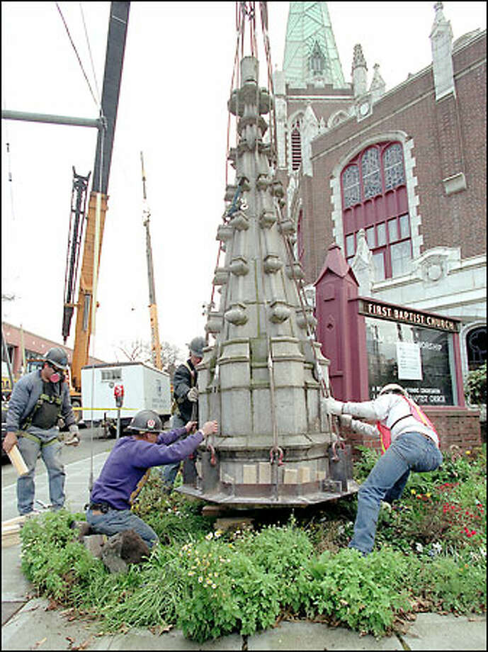 Workers from Nuprecon Demolition in Redmond lower one of four earthquake-damaged spires that flank the bell tower at Seattle's First Baptist Church to a temporary location at the corner of Seneca St. and Harvard Ave. Each spire is about 20 feet tall and weighs about 8,000 pounds. Photo: Gilbert W. Arias, Seattle Post-Intelligencer / Seattle Post-Intelligencer