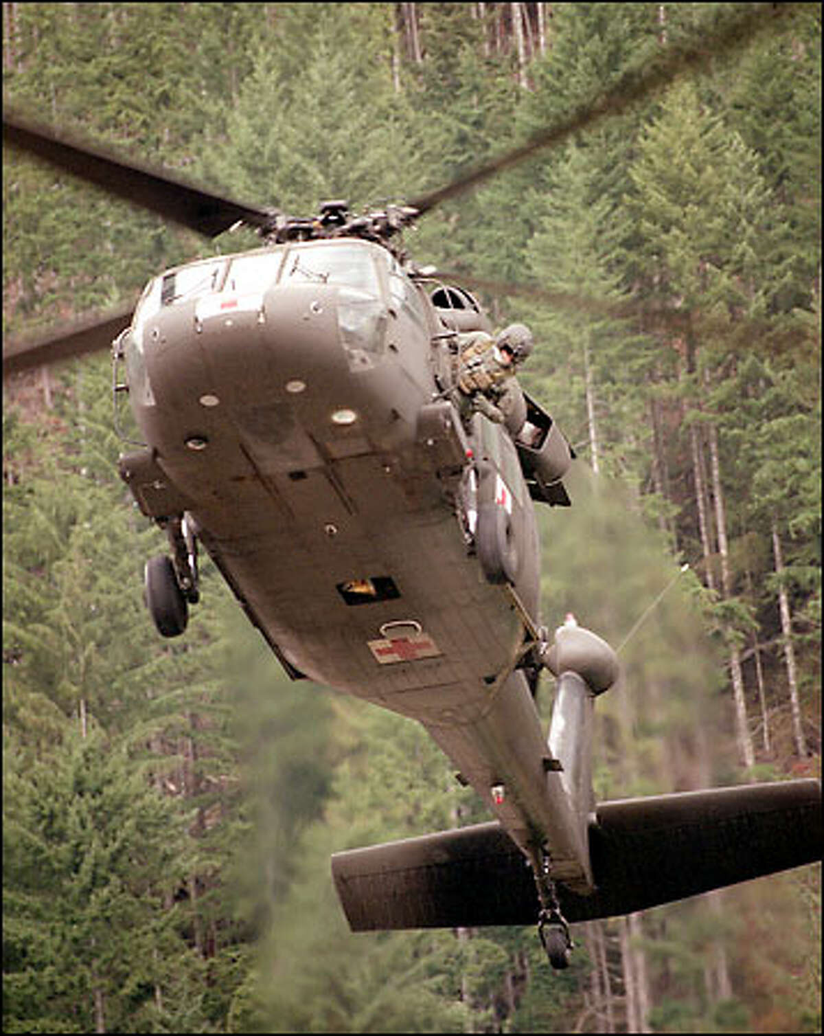 Sgt. Noah Harrison, US Army flight medic, makes sure the landing space below a 54th Medical Co. Blackhawk helicopter is clear during a Vision 2001 region training conference flying demonstration at the North Bend Fire Academy.
